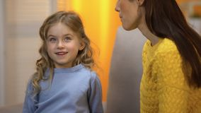 Funny little curly-haired girl talking to babysitter, telling about her dreams. Stock footage stock video footage