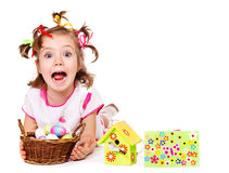 Funny little girl. Holding wicker basket with Easter eggs royalty free stock images