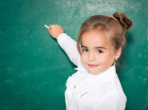 Funny little girl. Portrait of smart schoolchild by the blackboard looking at camer Royalty Free Stock Image
