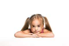 Funny little girl. Little girl looking down on white poster Royalty Free Stock Photography