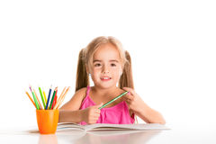 Funny little girl. Little girl drawing with crayons on a white background Royalty Free Stock Photography