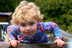Funny Little Girl. Cute little girl with blond hair leaning over and giving a funny look toward the camera Stock Photography