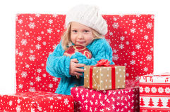 Funny little girl around christmas gift boxes Royalty Free Stock Photos