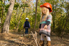 Funny little girl arranging sticks for a fire camp Stock Image
