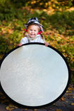 Funny little girl assist the photographer. With reflector Stock Photography