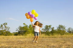 Funny little girl with balloons, bouncing Royalty Free Stock Photo