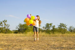 Funny little girl with balloons, bouncing Royalty Free Stock Photography