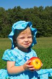 Funny little girl with a big apple Royalty Free Stock Photos