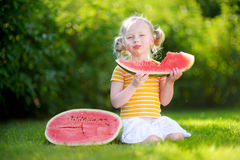 Funny little girl biting a slice of watermelon outdoors. On warm and sunny summer day stock image