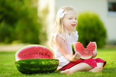 Funny little girl biting a slice of watermelon outdoors on warm and sunny summer day Stock Photos