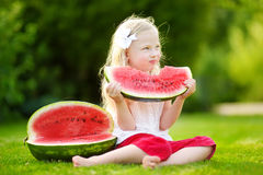 Funny little girl biting a slice of watermelon outdoors on warm and sunny summer day Stock Image