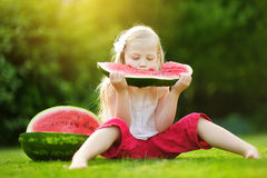 Funny little girl biting a slice of watermelon outdoors on warm and sunny summer day Stock Photography