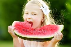 Funny little girl biting a slice of watermelon outdoors on warm and sunny summer day Royalty Free Stock Images