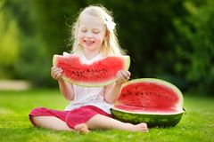 Funny little girl biting a slice of watermelon outdoors on warm and sunny summer day Royalty Free Stock Photography