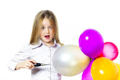 Funny little girl blowing up colorful baloons Royalty Free Stock Photo