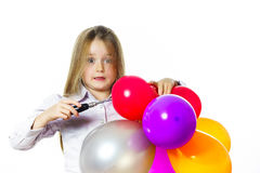 Funny little girl blowing up colorful baloons Royalty Free Stock Images