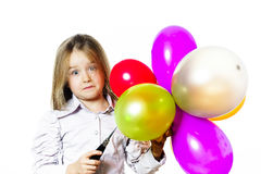 Funny little girl blowing up colorful baloons Royalty Free Stock Photos