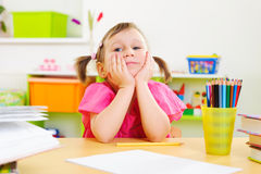 Funny little girl leaning on cheeks Royalty Free Stock Photo