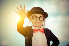 Funny little girl in bow tie and bowler hat with hello gesture. Royalty Free Stock Images