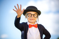 Funny little girl in bow tie and bowler hat with hello gesture. Retro stile Stock Photo
