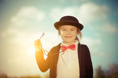 Funny little girl in bow tie and bowler hat. Stock Photo