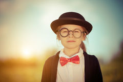 Funny little girl in bow tie and bowler hat. Royalty Free Stock Image