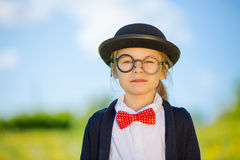 Funny little girl in bow tie and bowler hat. Stock Photos