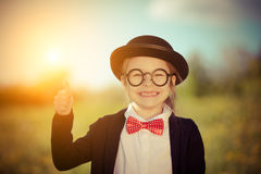 Funny little girl in bow tie and bowler hat showing thumb up. Royalty Free Stock Images