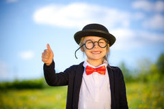 Funny little girl in bow tie and bowler hat showing thumb up. Royalty Free Stock Photos