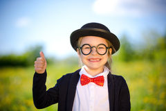 Funny little girl in bow tie and bowler hat showing thumb up. Royalty Free Stock Photo