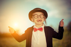 Funny little girl in bow tie and bowler hat showing thumbs up. Royalty Free Stock Photos