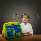 Funny little girl with braided hair up, big glasses. Beside her plate Back to School subtitles Royalty Free Stock Photo