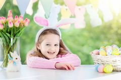 Funny little girl in bunny ears at breakfast stock photos