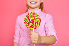 Funny little girl with candy lollipop. Happy little girl holding a candy. Royalty Free Stock Photos