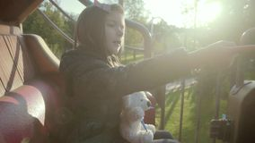 Funny little girl on carousel ride in yellow carruseles caravan in park stock video