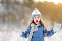 Funny little girl catching snowflakes in winter park Royalty Free Stock Photo