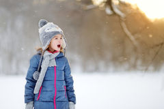 Funny little girl catching snowflakes in winter park Royalty Free Stock Image