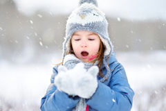 Funny little girl catching snowflakes in winter park Stock Photography