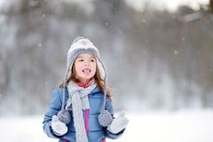 Funny little girl catching snowflakes in winter park Royalty Free Stock Photography