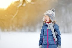 Funny little girl catching snowflakes in winter park Royalty Free Stock Photos