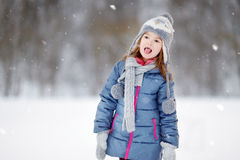 Funny little girl catching snowflakes in winter park Stock Images