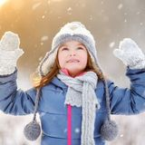 Funny little girl catching snowflakes in winter park Stock Photos