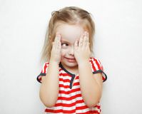 Funny little girl that cheats in hide and seek game. Funny little girl in striped T-shirt that cheats in hide and seek game. Child covers half of face with palm Royalty Free Stock Photo