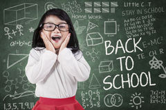 Funny little girl in classroom Stock Photos