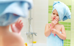 Funny little girl cleans teeth with toothbrush in bathroom Stock Image