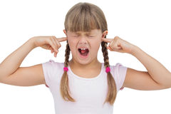 Funny little girl clogging her ears and wincing. On white background Royalty Free Stock Image