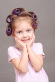 Funny little girl with curlers Stock Photography