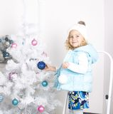 Funny little girl is decorating Christmas tree Stock Image