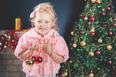 Funny little girl decorating Christmas tree Royalty Free Stock Photography