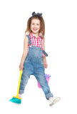 Funny little girl in denim overalls sweeping the Royalty Free Stock Images